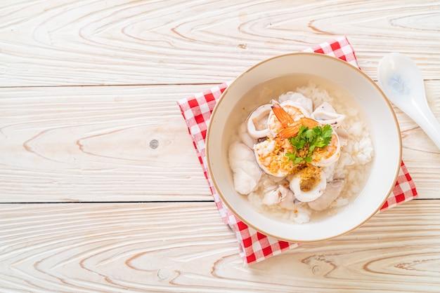Tigela de sopa de mingau ou arroz cozido com frutos do mar (camarão, lula e peixe)