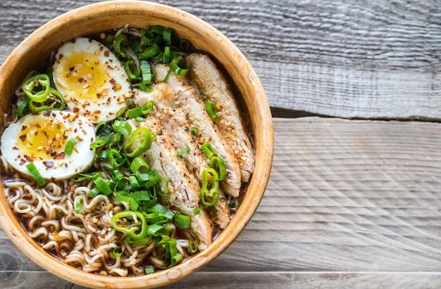 Tigela de sopa de ramen de galinha na mesa de madeira