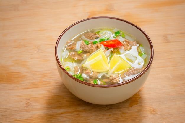 Tigela de sopa picante de pho com carne bovina, fatia de limão e pimenta malagueta na mesa de madeira. entrega ao domicílio