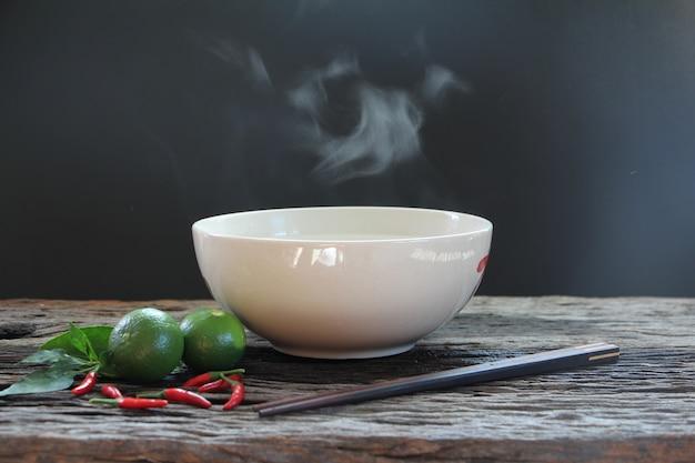 Tigela de sopa quente com vapor na mesa de madeira