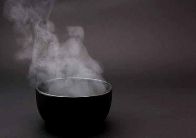 Tigela de sopa quente em preto