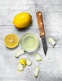 Tigela de suco de limão com as raspas de um limão e uma faca. em superfície rústica