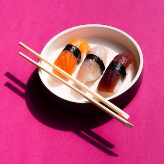 Tigela de sushi branco com pauzinhos no fundo rosa