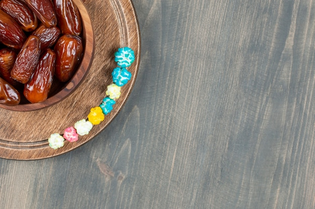 Tigela de tâmaras e pipocas na placa de madeira