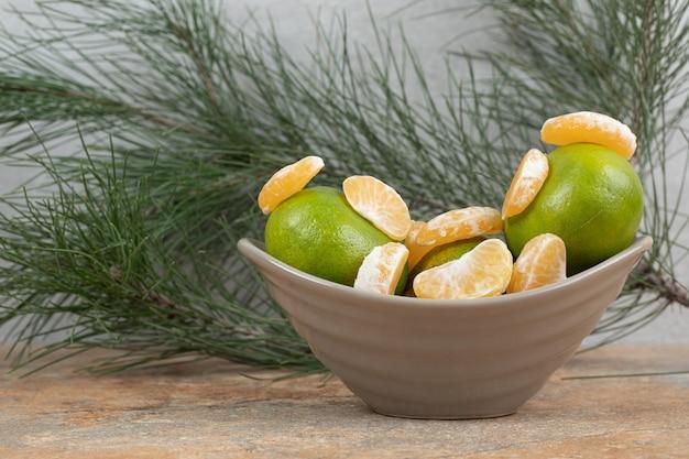 Tigela de tangerina fresca e segmentos na mesa de mármore.