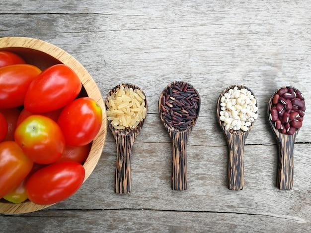 Tigela de tomate semente colher de madeira grãos sementes de cereais vários tipos de feijão vermelho trabalho lágrimas r