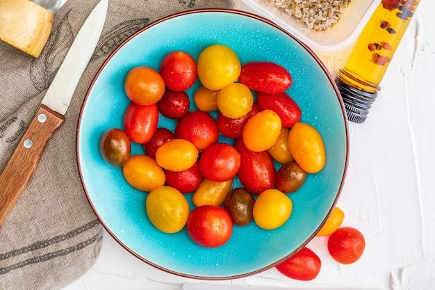 Tigela de tomates-cereja coloridos (vermelho, granada e amarelo), frescos e crus.
