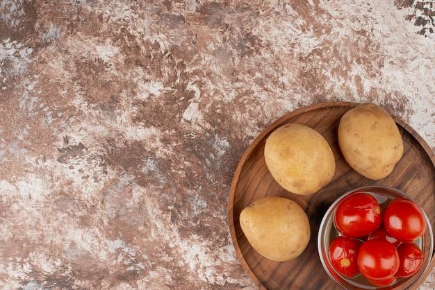 Tigela de tomates em conserva e batatas cozidas na mesa de mármore.