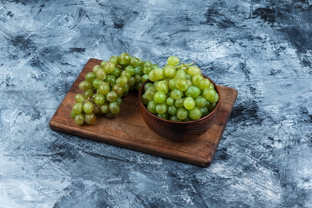 Tigela de uvas em uma placa de corte em um fundo de mármore azul escuro. vista de alto ângulo.