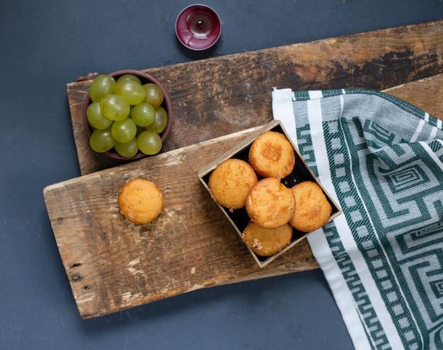 Tigela de uvas verdes e bolos no pedaço de madeira