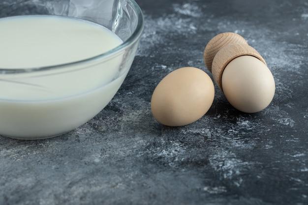 Tigela de vidro cheia de leite fresco e ovos em mármore.