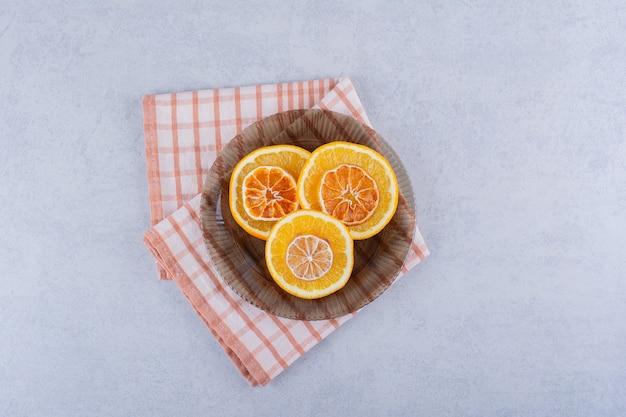 Tigela de vidro com fatias de laranja frescas e secas na mesa de pedra.