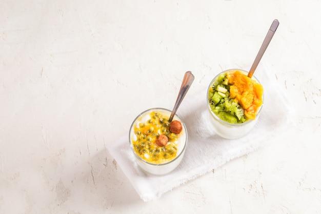 Tigela de vidro com iogurte e frutas fatiadas no guardanapo branco