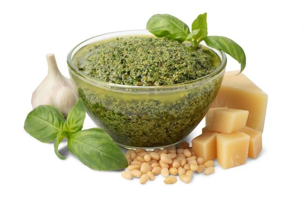 Tigela de vidro com molho pesto verde e ingredientes isolados no fundo branco