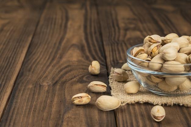 Tigela de vidro com pistache em um pedaço de serapilheira em uma mesa de madeira.