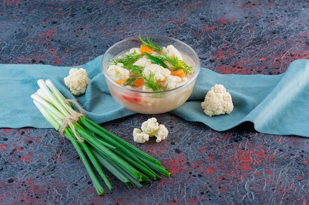 Tigela de vidro com sopa de vegetais orgânicos na superfície de mármore