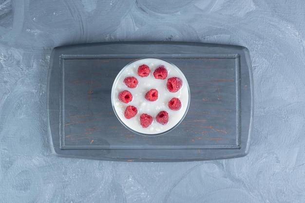 Tigela de vidro de arroz com leite com cobertura de framboesa em uma bandeja da marinha sobre fundo de mármore.