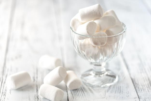 Tigela de vidro de marshmallows na madeira