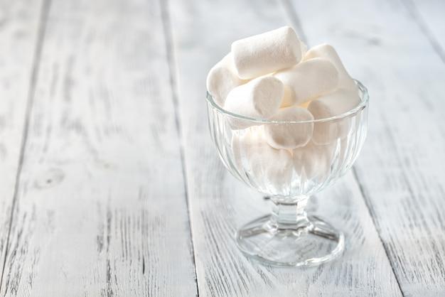 Tigela de vidro de marshmallows no fundo de madeira