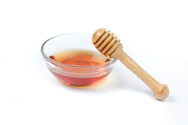 Tigela de vidro de mel puro com colher de pau de mel isolada no fundo branco