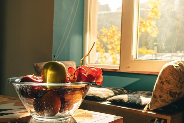 Tigela de vidro de variedade de frutas na mesa de madeira com luz quente.