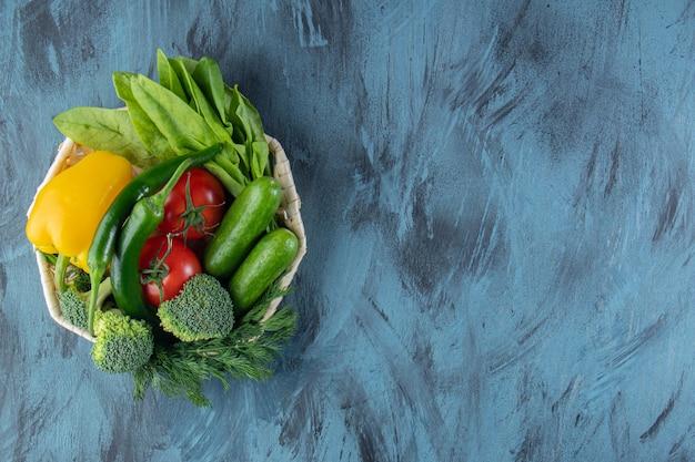 Tigela de vime de vegetais orgânicos frescos sobre fundo azul.