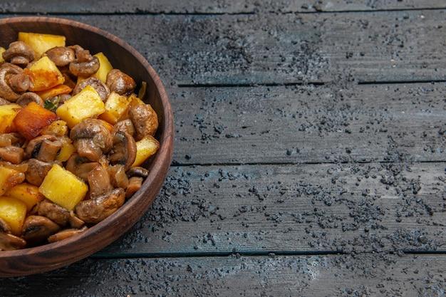 Tigela de vista de cima com tigela de madeira para comida com batatas e cogumelos no lado esquerdo da mesa