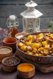 Tigela de vista lateral próxima com prato de comida com cogumelos fritos e batatas no quadro e especiarias coloridas e óleo