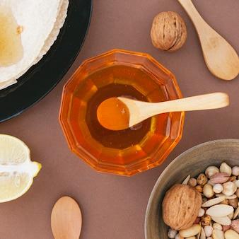 Tigela de vista superior arquivada com mel em cima da mesa