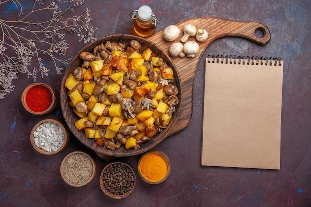 Tigela de vista superior com batatas e cogumelos tigela com batatas e cogumelos, óleo de cogumelos brancos em garrafa especiarias coloridas e um caderno