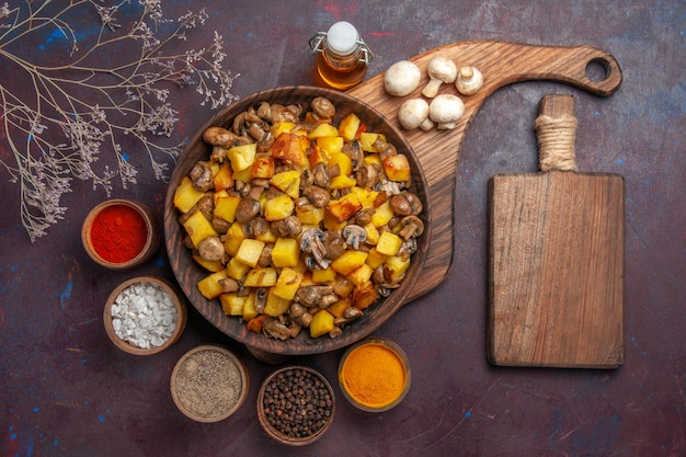 Tigela de vista superior com batatas e cogumelos tigela com batatas e cogumelos óleo de cogumelos brancos em garrafa especiarias coloridas e uma tábua de cortar