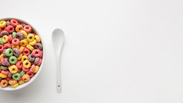 Tigela de vista superior com colher de cereal e plástico