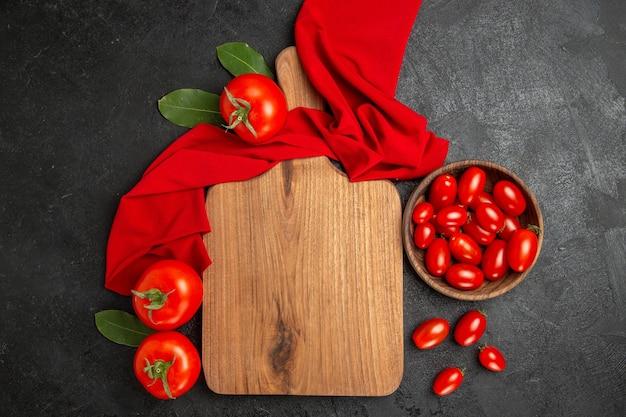 Tigela de vista superior com tomate cereja, toalha vermelha, tábua de cortar e tomates vermelhos em fundo escuro