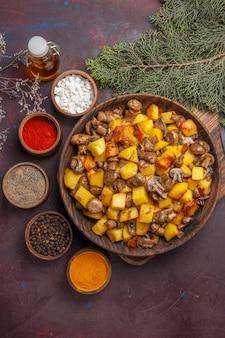 Tigela de vista superior próxima com tigela de comida com cogumelos fritos e batatas, especiarias diferentes e óleo ao lado dos galhos e cones