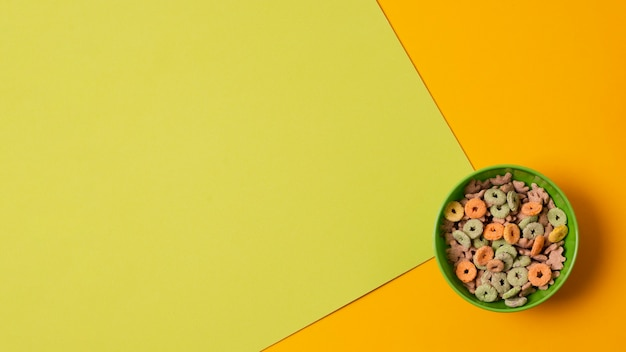 Tigela de vista superior verde com cereais coloridos