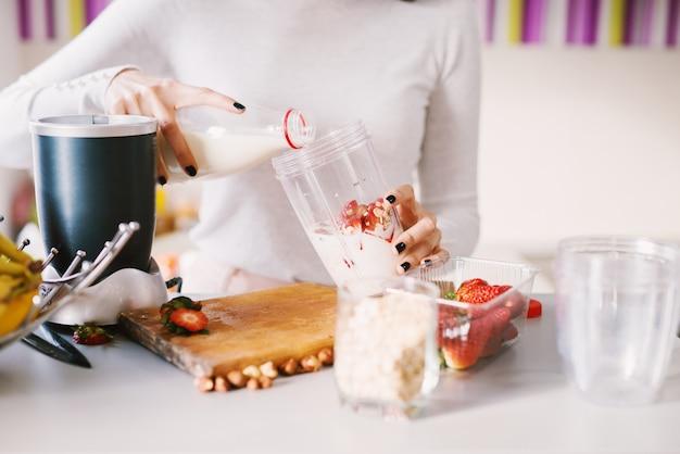 Tigela dobradeira branca está sendo preenchida com ingredientes frescos para um smoothie perfeito.