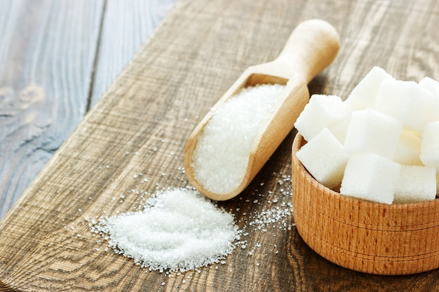 Tigela e colher com areia branca e açúcar protuberância em fundo de madeira