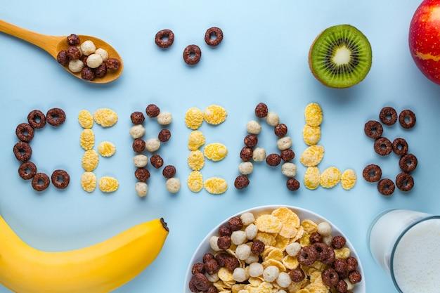 Tigela e colher com bolas de chocolate secas, anéis, flocos de milho, copo de leite e frutas frescas maduras para o café da manhã saudável de cereais de fibra. conceito de cereais