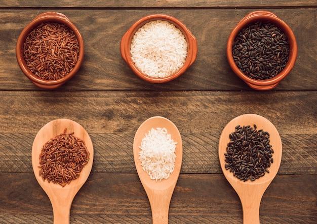 Tigela e colher de pau com branco; grãos de arroz vermelho e preto na mesa de madeira