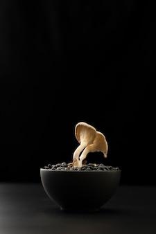 Tigela escura com feijão e cogumelos em uma mesa escura