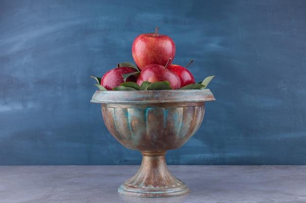 Tigela escura com maçãs vermelhas brilhantes na superfície da pedra.