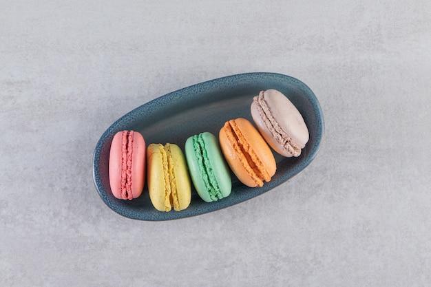 Tigela escura de macaroons doces coloridos na mesa de pedra.