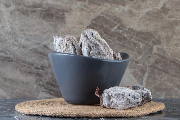 Tigela escura de saborosos caquis secos em fundo de mármore.