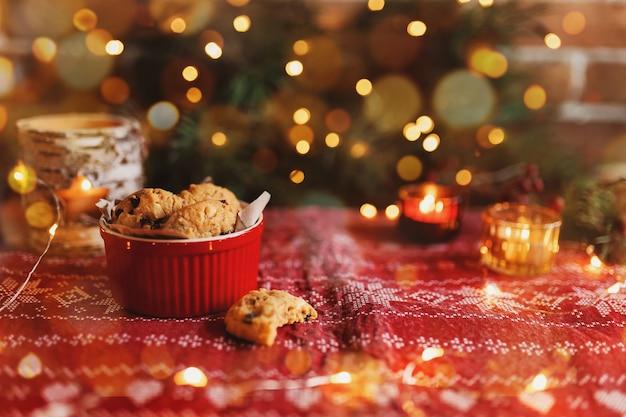 Tigela festiva vermelha cheia de biscoitos de natal desfocando as luzes da árvore de natal
