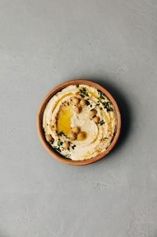 Tigela grande de hummus caseiro, guarnecida com grão de bico, pimentão vermelho, salsa e azeite
