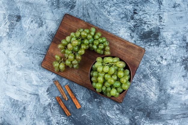 Tigela leiga plana de uvas na tábua com canela em fundo de mármore azul escuro. horizontal