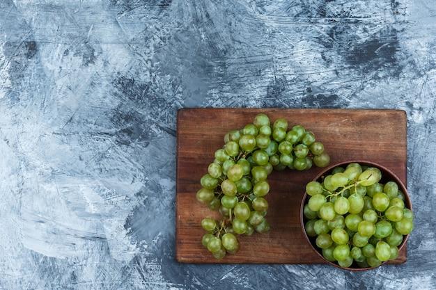 Tigela leiga plana de uvas na tábua em fundo de mármore azul escuro. horizontal