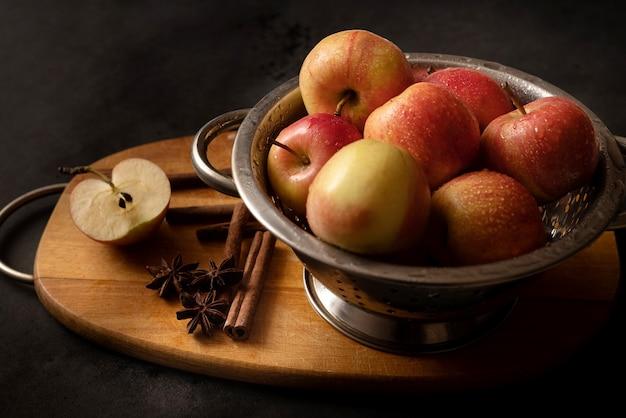 Tigela metálica cheia de maçãs vermelhas maduras espalhadas em paus de canela estrelas de aniis uma metade de maçã em uma tábua de madeira natureza morta ingridientes de torta de maçã cozinhar em casa