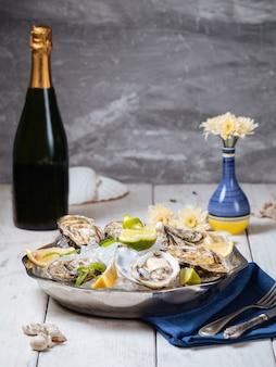 Tigela metálica com ostras frescas, gelo, limão e uma garrafa de champanhe