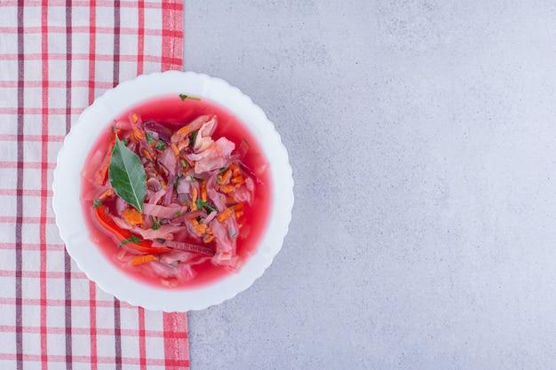 Tigela muito quente de sopa de beterraba com cobertura de folha de louro em uma toalha de mesa com fundo de mármore. foto de alta qualidade